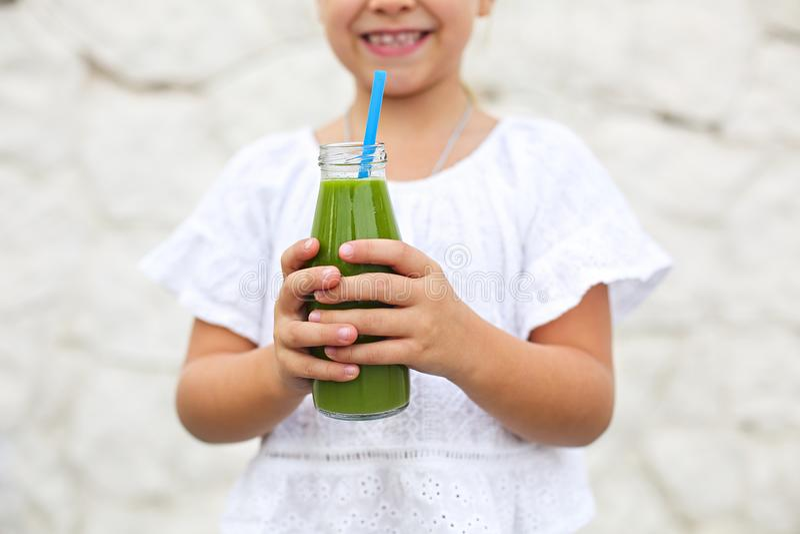 La niña está bebiendo el jugo fresco verde usando la paja al aire libre foto de archivo