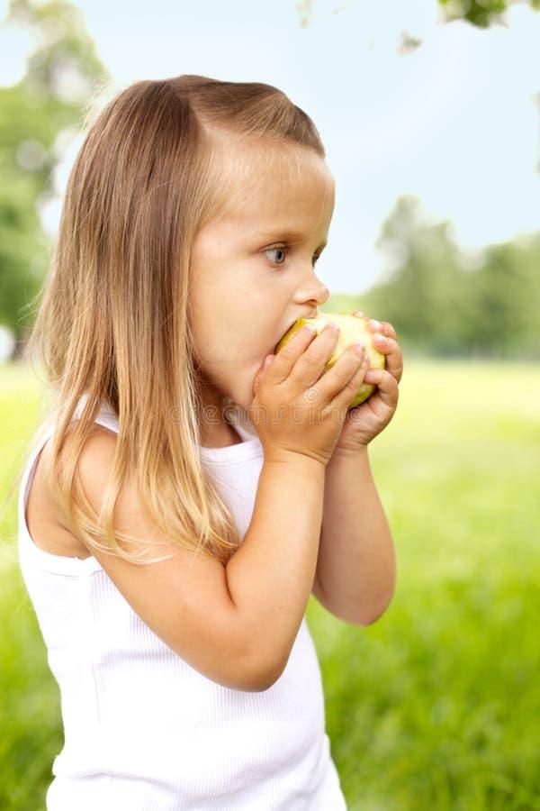 La niña está comiendo la manzana imagenes de archivo