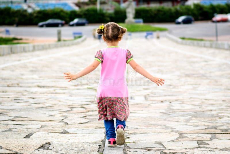 La niña está corriendo en la 'promenade' pavimentada piedra imagen de archivo libre de regalías