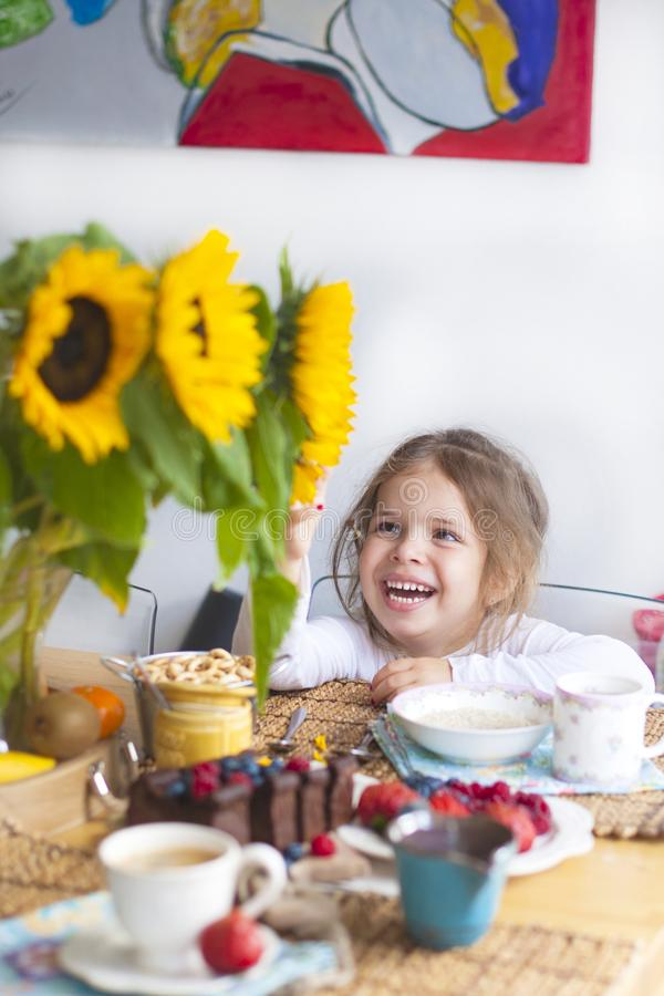 La niña está desayunando en casa En la tabla es un ramo de flores de girasoles y de una empanada dulce con la fruta, imagenes de archivo