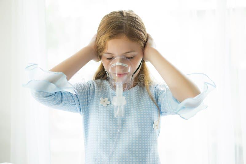 La niña está enferma usando máscara de oxígeno en su cara mientras que su Han fotos de archivo