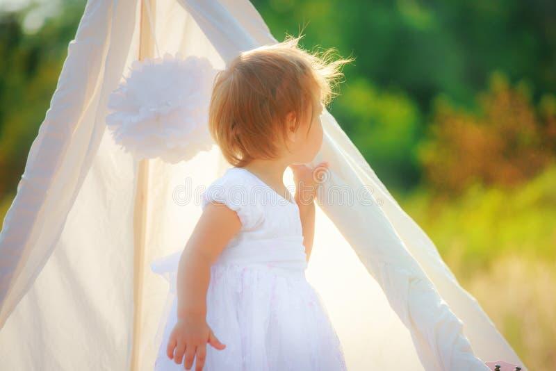 La niña está haciendo una pausa la choza blanca a la naturaleza y mira hacia fuera para él Bebé hermoso con el pelo corto en vest fotografía de archivo libre de regalías