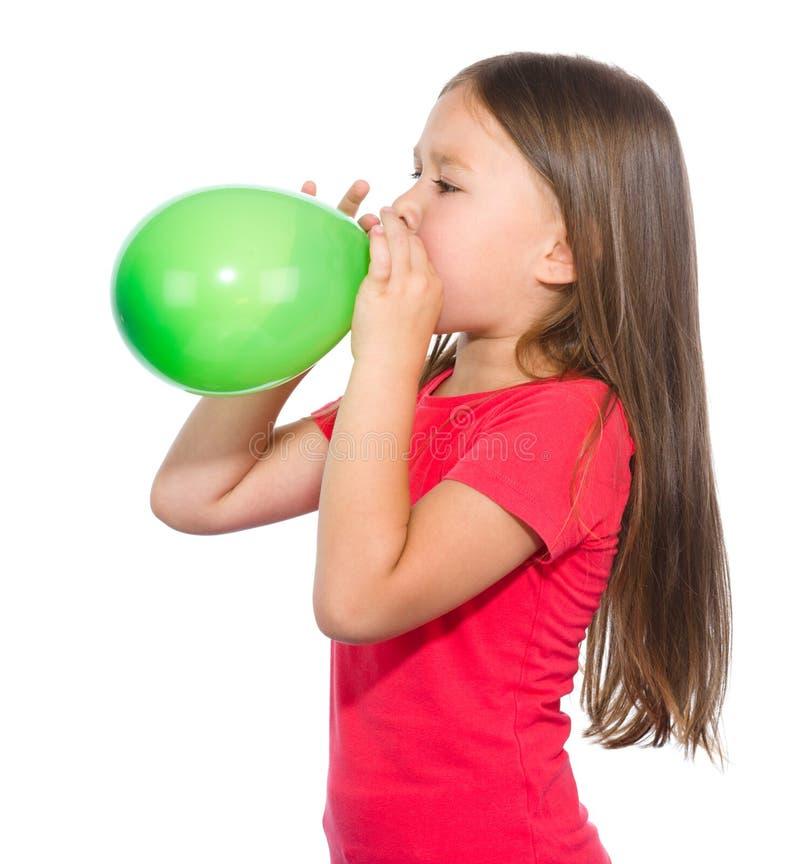 La niña está inflando el globo verde foto de archivo