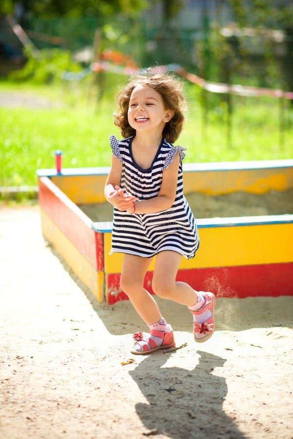 La niña está jugando con la arena en patio imagen de archivo