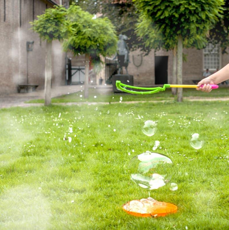 La niña está jugando con las burbujas de jabón en un parque en hierba verde Niñez feliz y juegos al aire libre Espacio libre para imagen de archivo