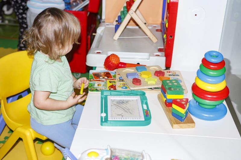 La niña está jugando con los juguetes en centro entretenido del ` s de los niños foto de archivo