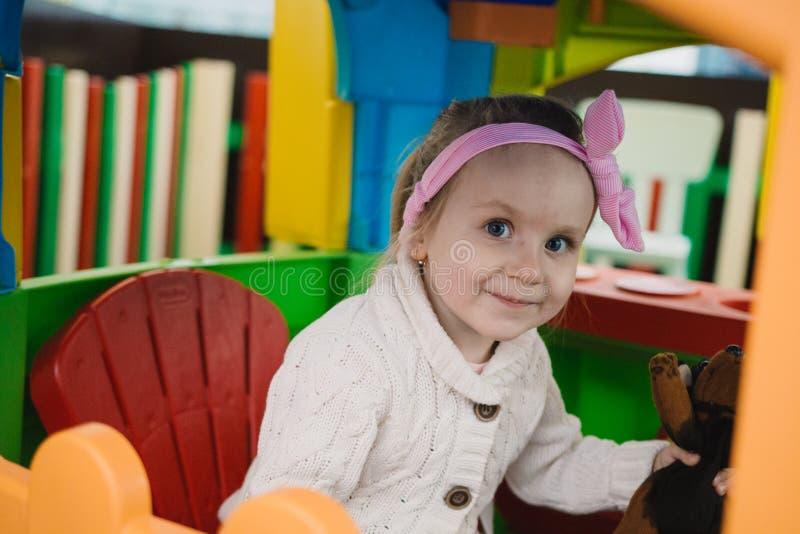 La niña está jugando con los juguetes en el cuarto del ` s de los niños imágenes de archivo libres de regalías