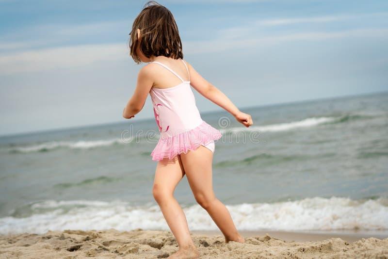 La niña está jugando en la arena en la playa fotos de archivo libres de regalías