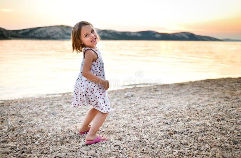 La niña está jugando en la playa arenosa en puesta del sol o salida del sol fotografía de archivo libre de regalías