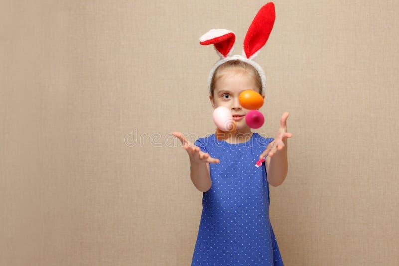 la niña está lanzando algunos huevos de Pascua imagen de archivo
