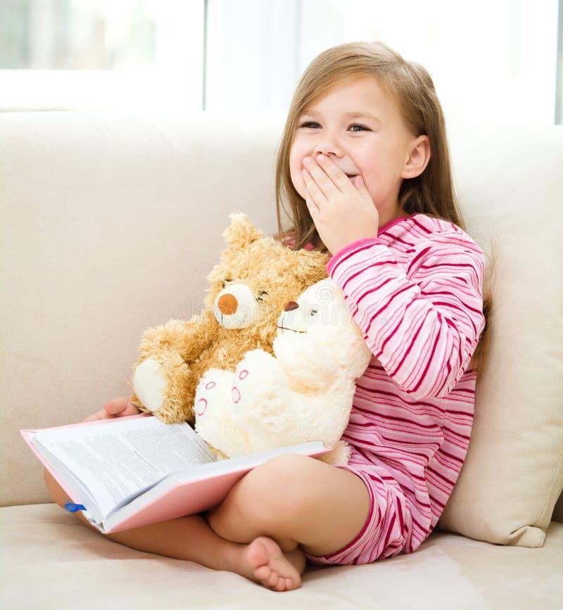 La niña está leyendo un libro para sus osos de peluche foto de archivo