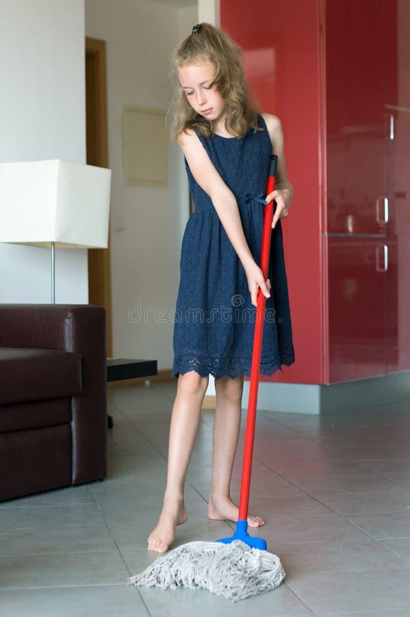 La niña está limpiando el apartamento imagenes de archivo
