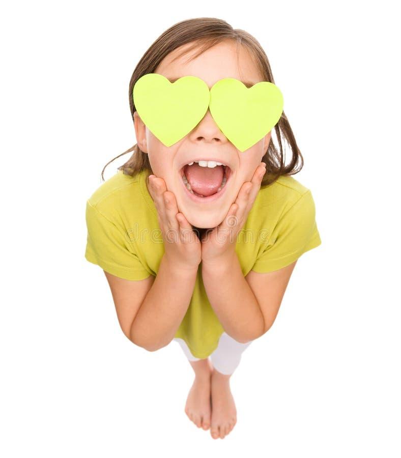 La niña está llevando a cabo corazones sobre sus ojos imagen de archivo libre de regalías