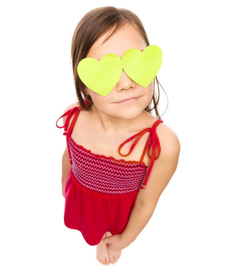 La niña está llevando a cabo corazones sobre sus ojos imagenes de archivo