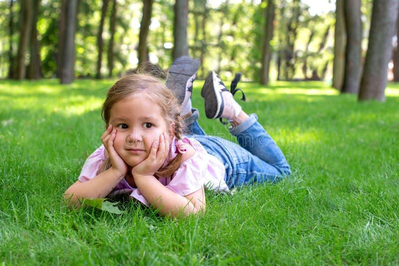 La niña está mintiendo en la hierba verde en el parque y el drea fotos de archivo