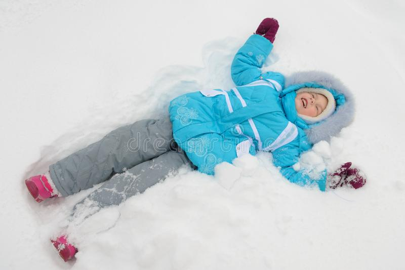 La niña está mintiendo en la nieve y la sonrisa imágenes de archivo libres de regalías