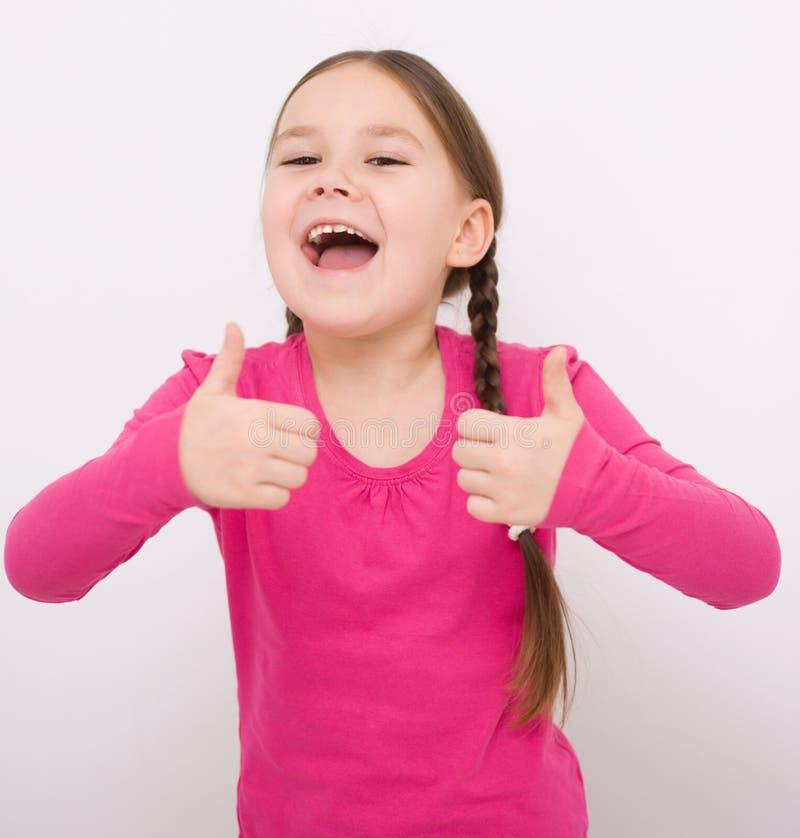 La niña está mostrando el pulgar encima del gesto imagenes de archivo