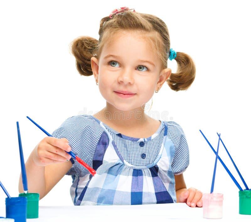 La niña está pintando con aguazo foto de archivo
