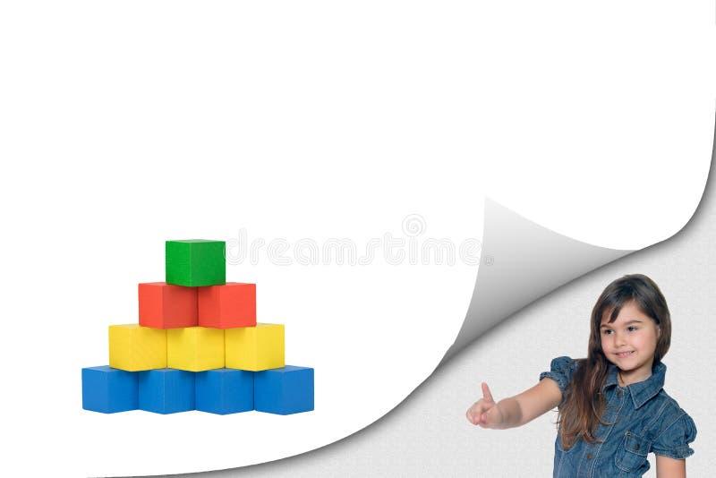 La niña está señalando en los cubos de madera juega imagenes de archivo