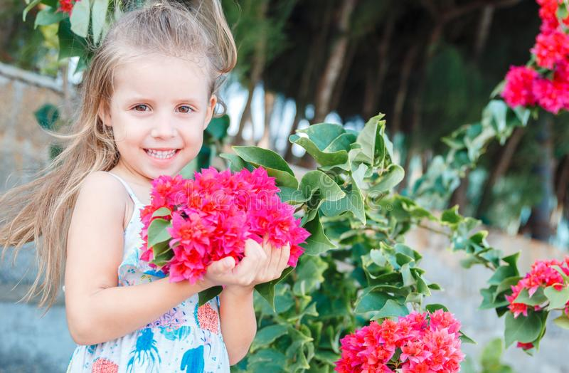 La niña está sosteniendo las flores rosadas hermosas bougainvillea imagen de archivo libre de regalías