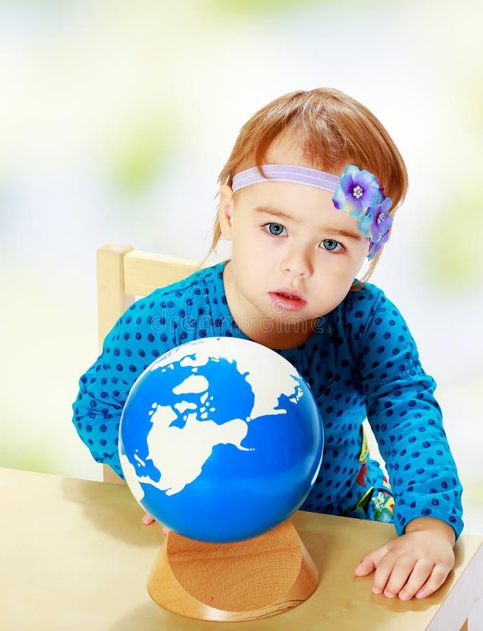La niña examina el globo foto de archivo libre de regalías