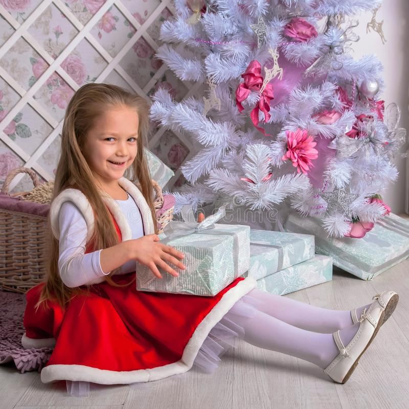La niña feliz abre regalos de Navidad imágenes de archivo libres de regalías