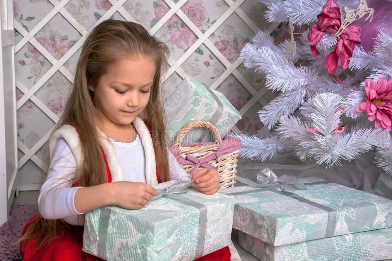 La niña feliz abre regalos de Navidad fotografía de archivo