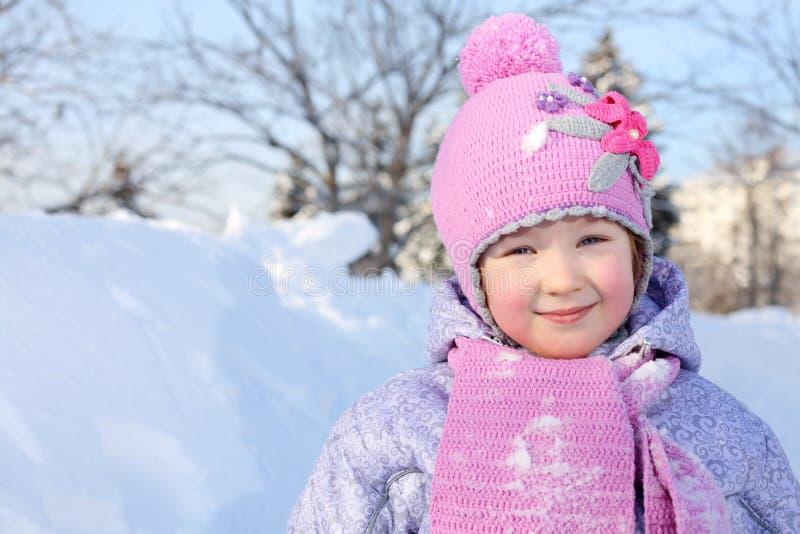 La niña feliz en bufanda y sombrero rosados mira la cámara foto de archivo