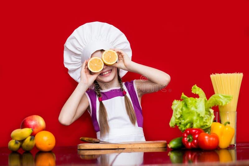 La niña feliz en uniforme del cocinero corta la fruta en cocina foto de archivo