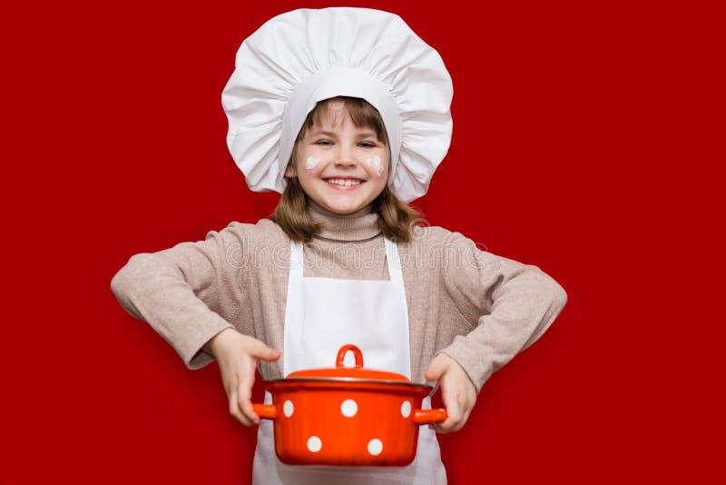 La niña feliz en uniforme del cocinero sostiene el cazo fotografía de archivo