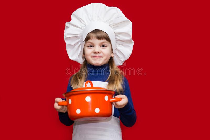 La niña feliz en uniforme del cocinero sostiene el cazo fotografía de archivo libre de regalías