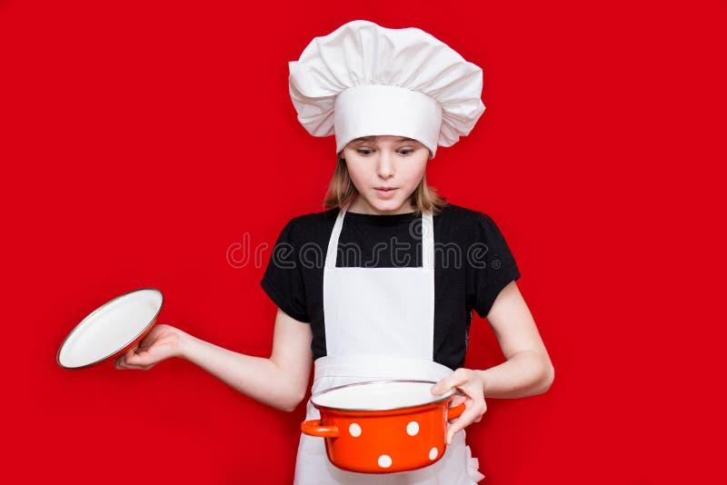 La niña feliz en uniforme del cocinero sostiene el cazo foto de archivo libre de regalías