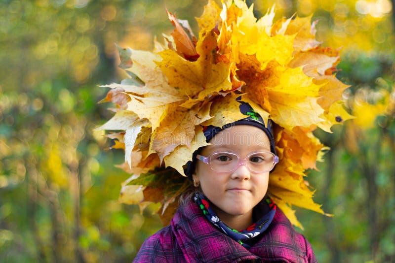 La niña feliz juega con las hojas de otoño en el parque foto de archivo