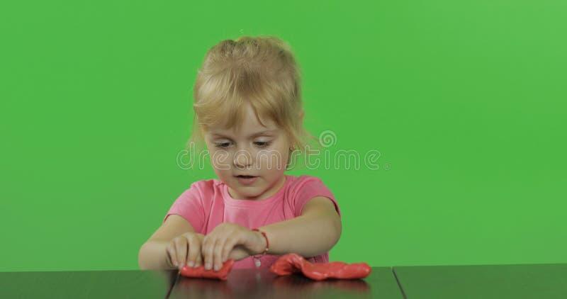La niña feliz juega con plasticine en el fondo dominante de la croma fotos de archivo