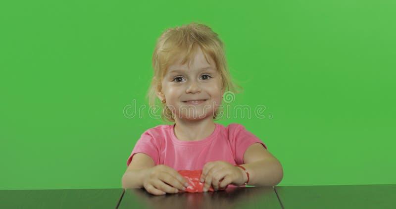 La niña feliz juega con plasticine en el fondo dominante de la croma fotos de archivo libres de regalías