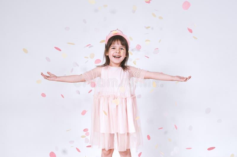 La niña feliz juguetona que lleva el vestido rosado en Tulle con la corona de la princesa en la cabeza en las manos blancas de la fotografía de archivo libre de regalías