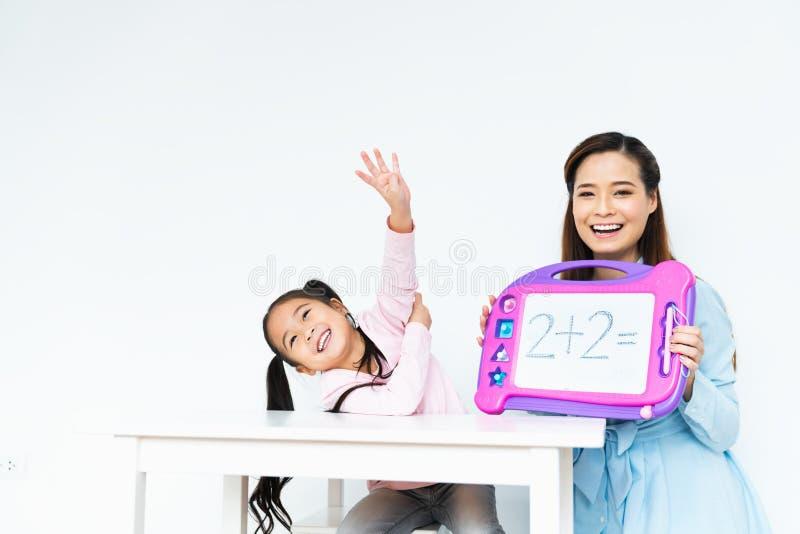 La niña feliz linda joven que aprende la ecuación matemática simple, madre asiática hermosa enseña usando tablero del juguete foto de archivo libre de regalías