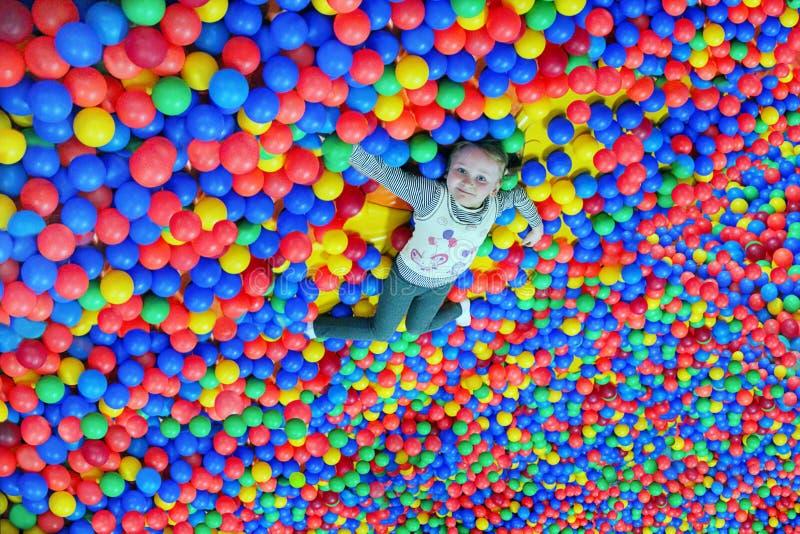 La niña feliz pone en el montón grande de pequeñas bolas multicoloras imagen de archivo