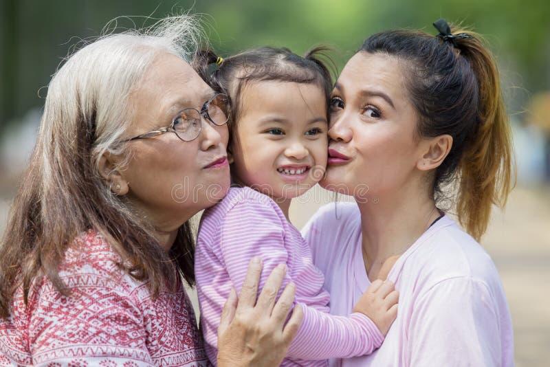 La niña feliz se besó por su madre y abuelita foto de archivo libre de regalías