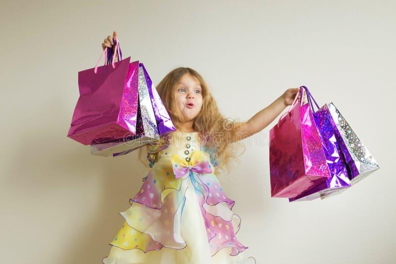 La niña feliz sorprendida sostiene muchos panieres de papel imagen de archivo libre de regalías