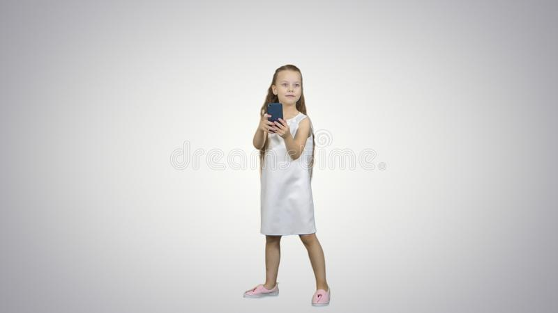La niña feliz toma un selfie con un teléfono elegante en el fondo blanco fotografía de archivo