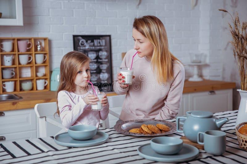 La niña feliz y su madre joven hermosa desayunan juntas en una cocina blanca Beben la leche y comen las galletas fotografía de archivo