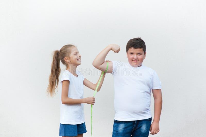 La niña fina bastante de risa que mide el bíceps gordo lindo del muchacho muscle con la cinta fotos de archivo