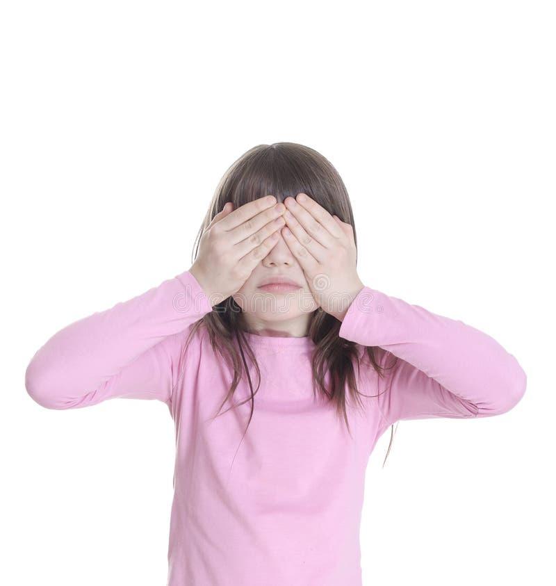 La niña ha cerrado las manos de los ojos fotografía de archivo libre de regalías