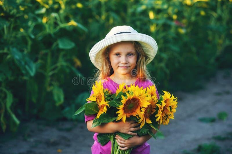 La niña hermosa en el sombrero brimmed ancho blanco con el girasol florece en el campo fotografía de archivo libre de regalías