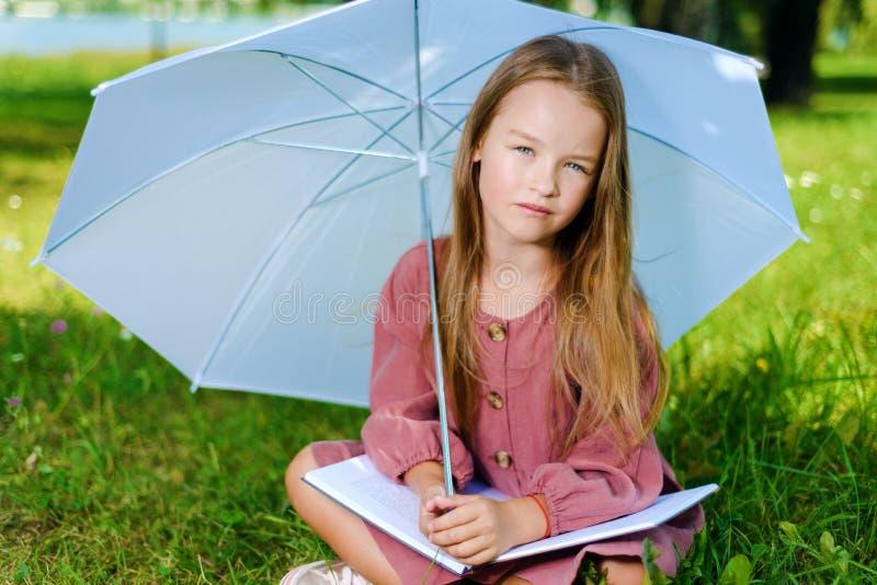 La niña hermosa en vestido rosado se sienta en parque en hierba en día soleado brillante foto de archivo