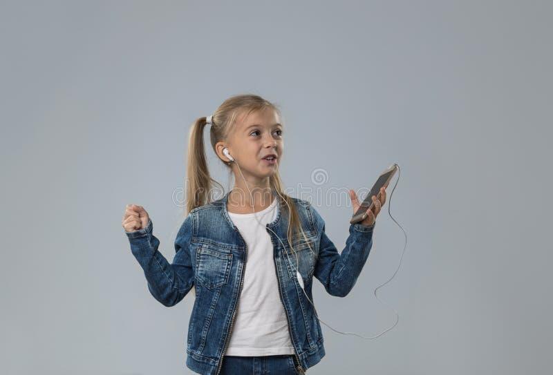 La niña hermosa que usa el teléfono elegante de la célula escucha sonrisa feliz de los auriculares del desgaste de la música aisl fotografía de archivo libre de regalías