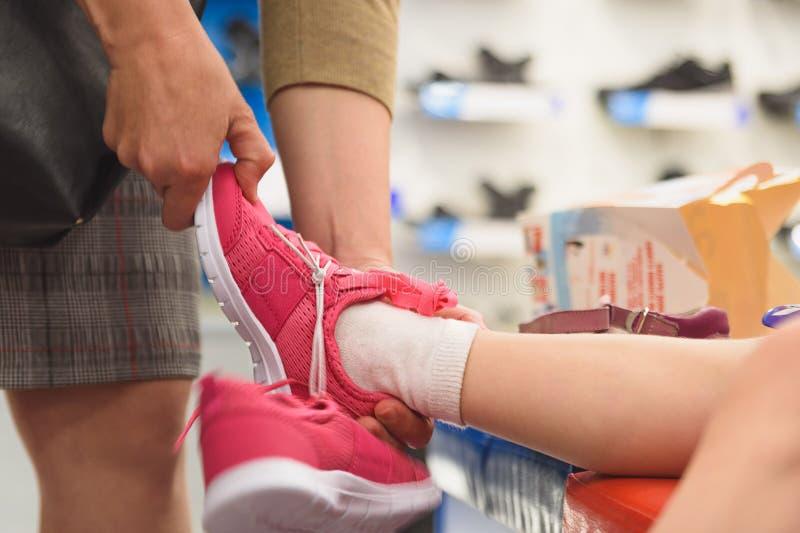 La niña intenta en el nuevo zapato en tienda foto de archivo