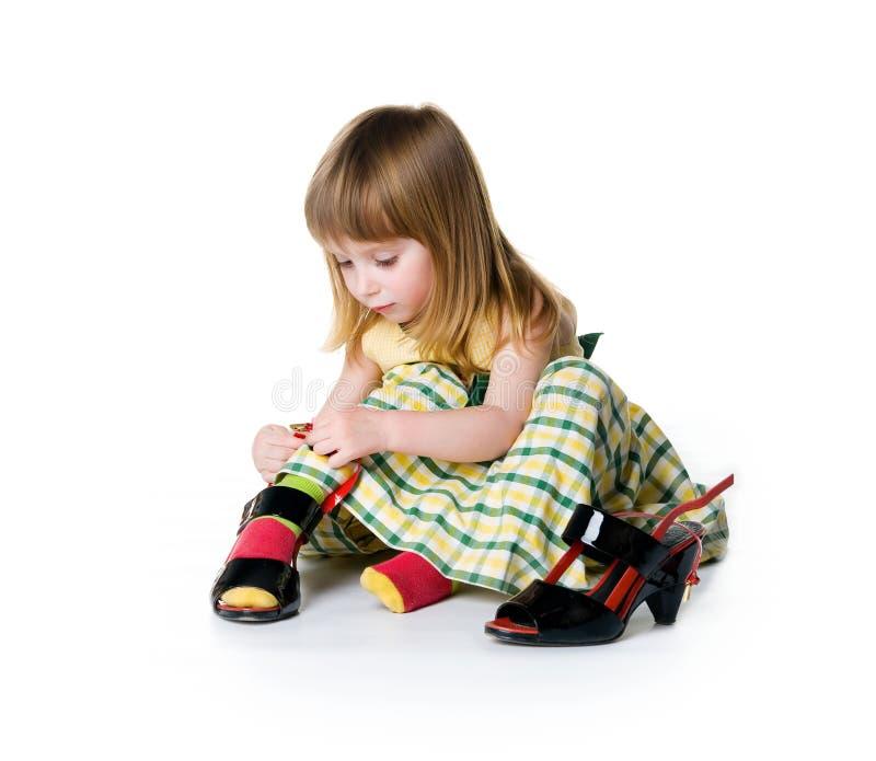 La niña intenta encendido los zapatos grandes fotos de archivo