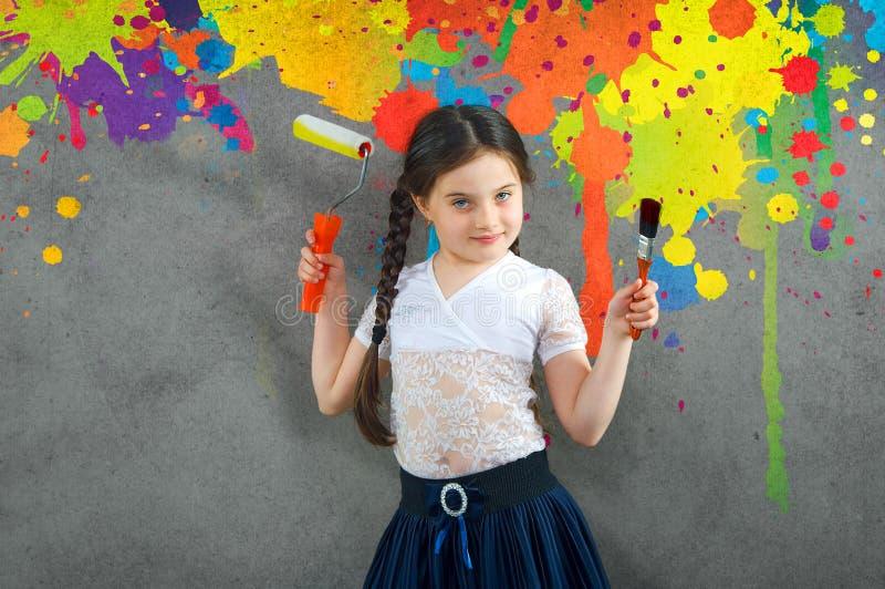 La niña joven sonriente alegre el niño dibuja en las pinturas coloreadas pared del fondo reparar creativos foto de archivo libre de regalías